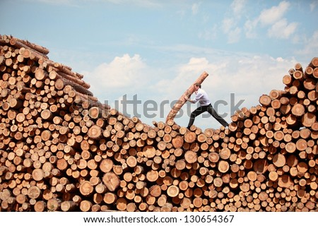business vision - hardworking businessman on top of large pile of cut wooden logs - stock photo