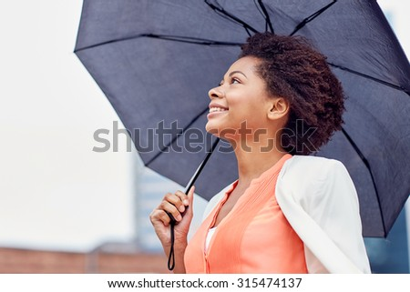 business, weather and people concept - young smiling african american businesswoman with umbrella on city street - stock photo