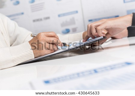 Business woman analyzing financial reports in the workplace of the company. - stock photo