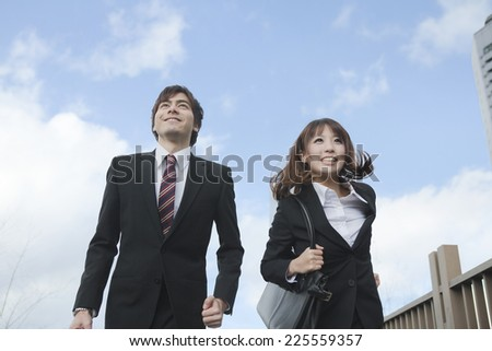 Business woman and business man are running through the front of the building - stock photo