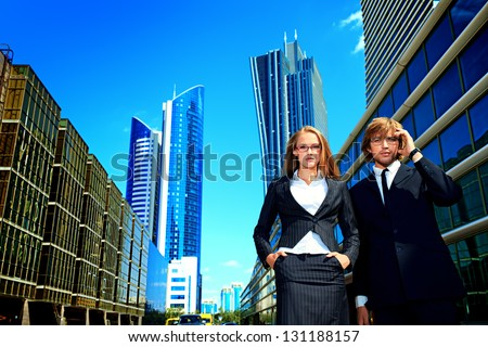 Business woman and business man is talking on mobile phone in front of skyscrapers. - stock photo