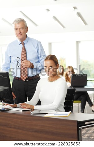 Business woman and businessman working together on laptop, while sitting at office.  - stock photo