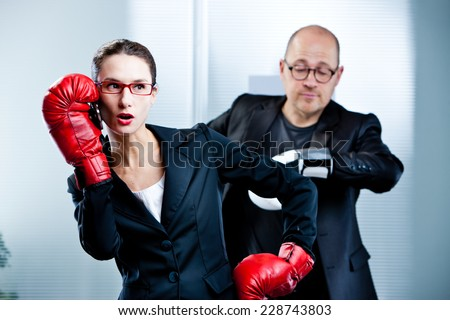 business woman answers the phone during a boxe match with a business man watching his watch impatiently - stock photo