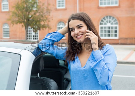 Business woman at the phone next to her new sports car - stock photo
