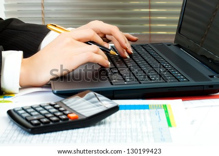business woman at workplace with laptop - stock photo
