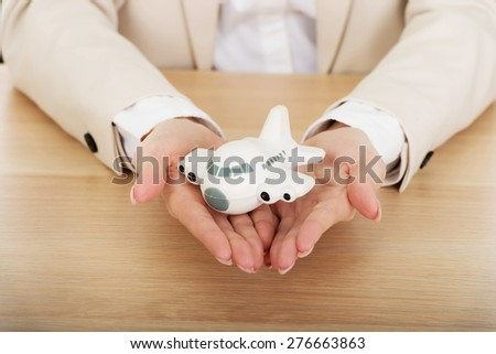 Business woman by a desk holding a toy plane. - stock photo