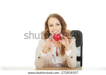 Business woman by a desk holding red heart.  - stock photo