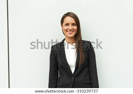 Business woman by the glass wall in the city smilingg at camera. - stock photo