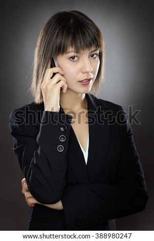 business woman chatting on a mobile phone low key lighting shot in the studio on a gray background - stock photo