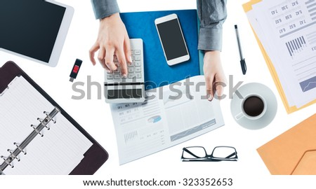 Business woman checking a financial report and calculating a balance, hands close up, top view - stock photo