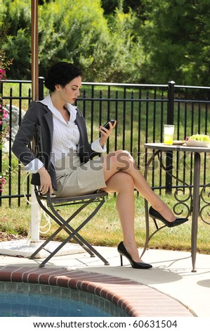 business woman checking her phone messages while sitting in an outdoor cafe - stock photo