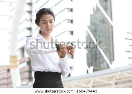 Business woman checking the time with modern building background - stock photo