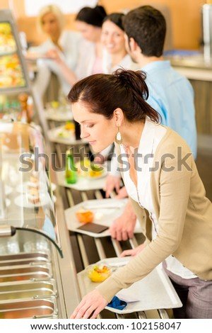 Business woman choose cafeteria lunch buffet carry serving tray - stock photo