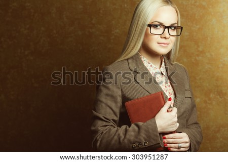 Business woman concept. Portrait of elegantly dressed young gorgeous blonde woman in trendy eyewear holding leather notebook posing over golden background. Smart casual style. Copy-space. Studio shot - stock photo