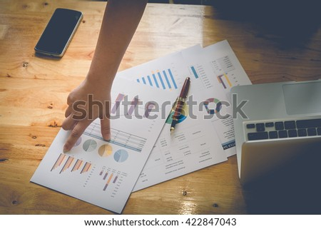 Business woman discussing graph on document with vintage retro filter - stock photo