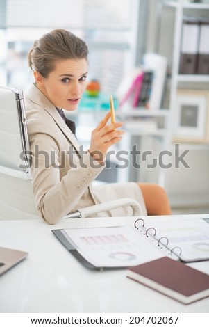 Business woman discussing in office and pointing in camera - stock photo