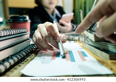 business woman documents on office table with smart phone and laptop and two colleagues discussing data in the background in morning light  - stock photo