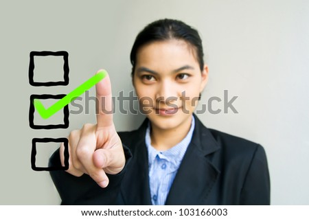 business woman drawing a tick on a glass - stock photo