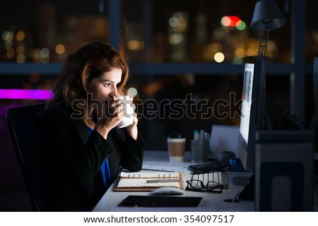 Business woman drinking coffee to get some energy for working overtime - stock photo