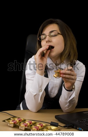 Business woman eating a chocolate - stock photo