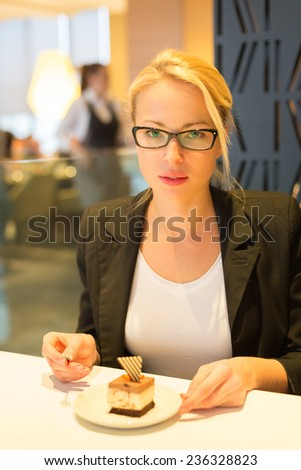 Business woman eating her favorite dessert in a fancy modern hotel restaurant. Unable to resist our sweet vices. Lifestyles. - stock photo