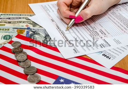 Business woman fills the tax form 1040 with money, pen, flag of USA and calculator - stock photo