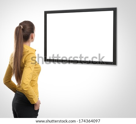 Business woman from the back looking at tv - stock photo