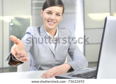 Business woman gives a handshake. Sitting near her laptop at her desk - stock photo