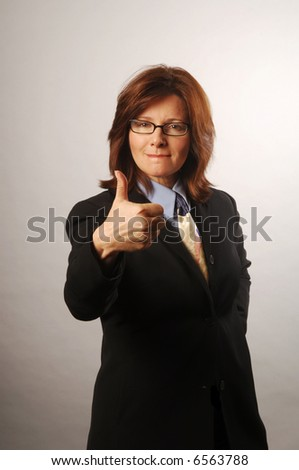 Business woman giving a thumbs up on the deal - stock photo