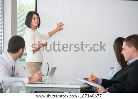 Business woman giving presentation to a team of her colleagues - stock photo