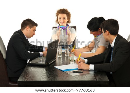 Business woman giving thumbs up at meeting while her colleagues working - stock photo