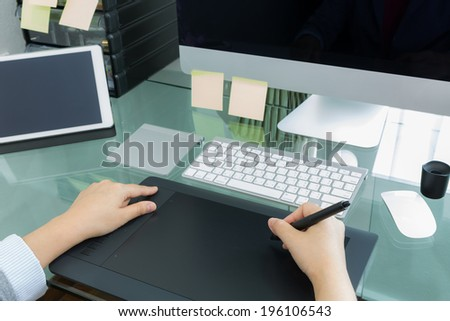 Business woman  graphic designer working in office using tablet pen - stock photo
