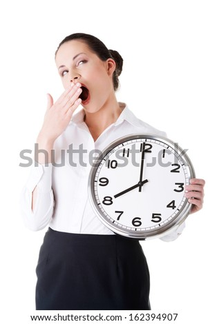 Business woman holding a clock and yeaning. Isolated on white.  - stock photo