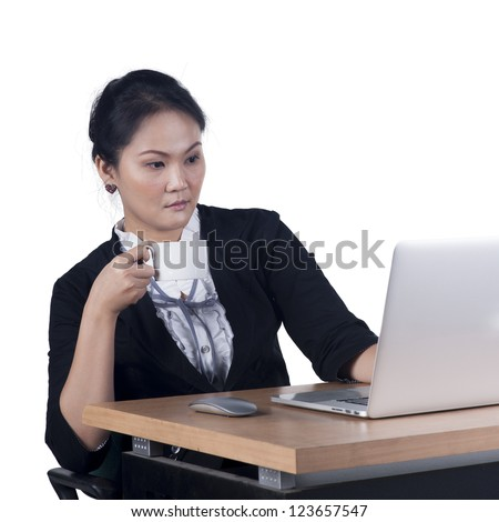 Business woman holding a cup of coffee and looking at laptop screen. Isolated white background. Model is Asian woman. - stock photo