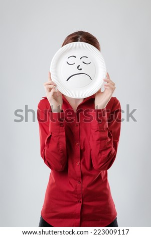 business woman holding a paper plate up to her face with a unhappy face drawn on plate - stock photo