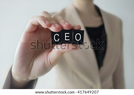 Business woman holding acronym CEO letter against a defocussed background with cool image temperature - stock photo