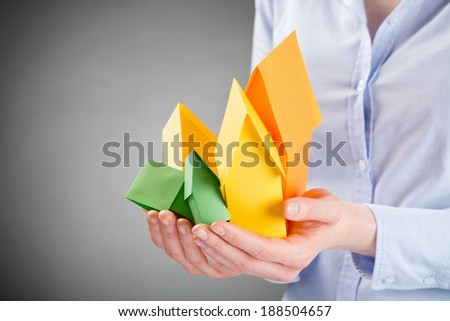 Business woman holding in her hands a pile of small paper houses in the colors of the European energy label standard. - stock photo