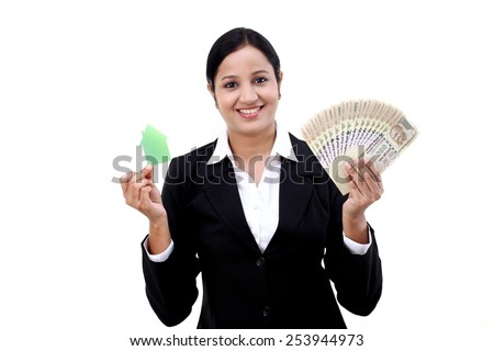 Business woman holding Indian currency and house model - stock photo