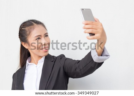 Business woman holding iphone. cellphone checking email  text messaging network lan internet looking selfie happy smiling mixed Asian tan Caucasian  busy Thailand asean white wall cement background - stock photo