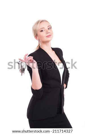 business woman holding keys over white background. Woman wearing black suit and smiling showing key - stock photo