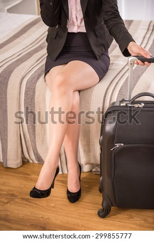 Business woman holding suitcase while sitting on bed at the hotel room. Close-up. - stock photo