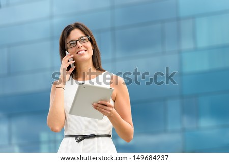 Business woman holding tablet pc computer and calling on cell phone outside corporate building. Caucasian hispanic female executive doing her job using digital communication technology. - stock photo