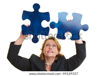 Business woman holding two blue jigsaw pieces - stock photo