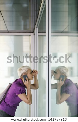 business woman in a hurry applying make up outdoor and looking at office building window - stock photo
