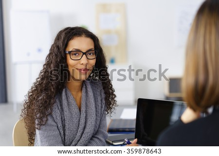 business woman in a meeting smiling at the camera - stock photo