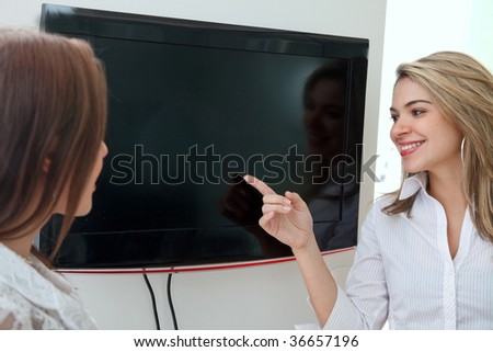 Business woman in an office pointing at a screen - stock photo