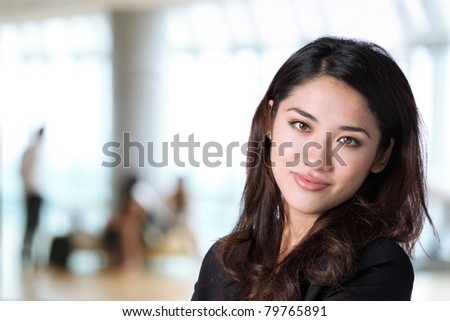 Business woman in corporate setting. The background is out of focus. - stock photo