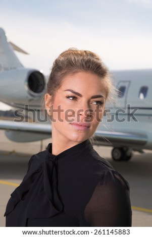 business woman in front of a corporate jet - stock photo