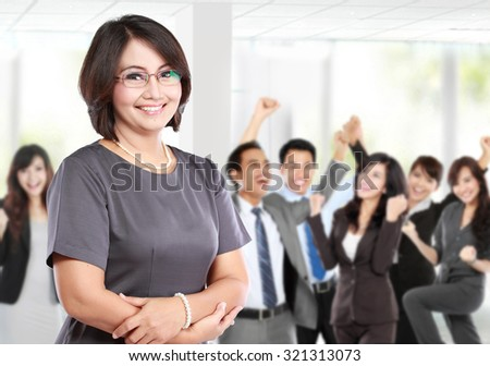 business woman in front of her team member, celebrating their success - stock photo