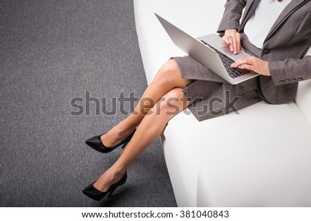 Business woman in high heels sitting on sofa with computer in her lap  - stock photo